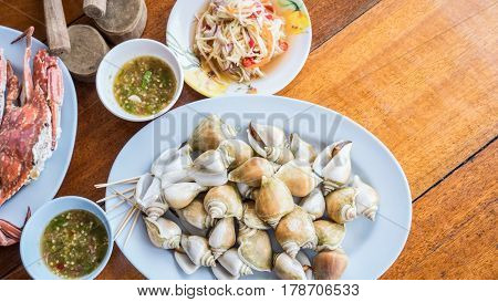 Boiled fresh Laevistrombus canarium or sea snail with raw mango salad and spicy seafood sauce