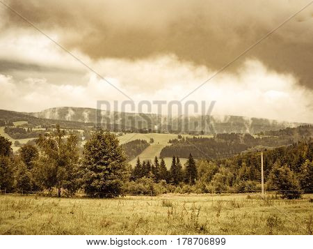 Aged nostalgic weathered vintage retro photo of cloudy misty landscape. mountain meadow and forests, both deciduous broadleaved and needle coniferous trees, electric overhead power line and horizon covered in clouds and mist, Czech republic, central Europ