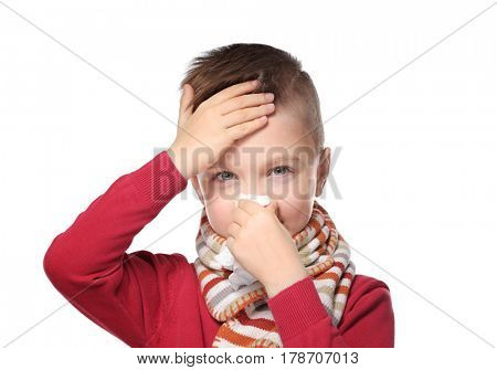 Cute little boy blowing his nose into tissue on white background