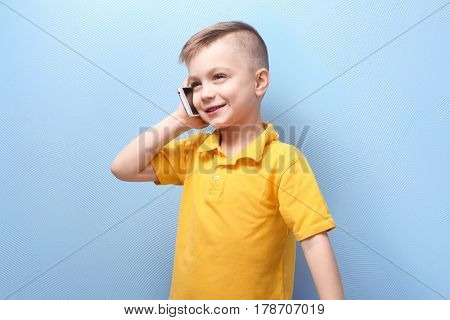 Cute little boy talking by mobile phone on color background