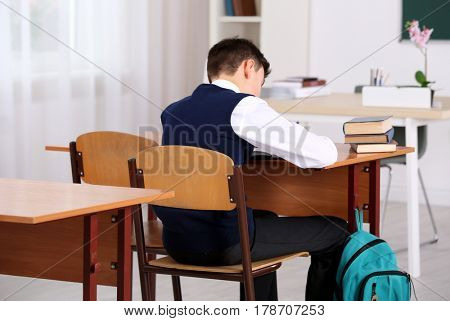 Incorrect posture concept. Schoolboy sitting at desk in classroom