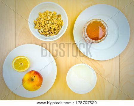Four ingredients for a healthy and nutritious snack or smoothie, apple lemon fruit, cottage cheese, honey , shelled nuts walnuts, on plates from top view, arranged on wooden table in soft colours