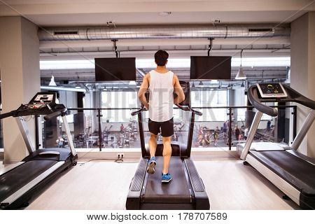 Young hispanic fitness man in sports clothing in gym doing cardio workout, exercising on treadmill. Sport fitness and healthy lifestyle concept. Rear view.