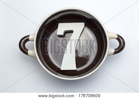 The number seven at the bottom of the soup tureen on white background.
