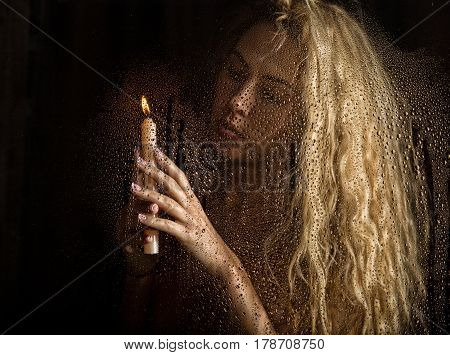 curly nude blonde woman with candle on dark background.