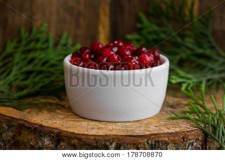 Pickled cranberries in a sweet syrup in a white bowl on the wooden background with the leaves of juniper.