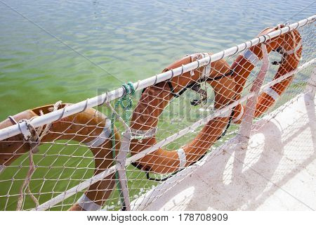 Three lifebuoy on ferry board with green river waters at bottom Huelva Spain