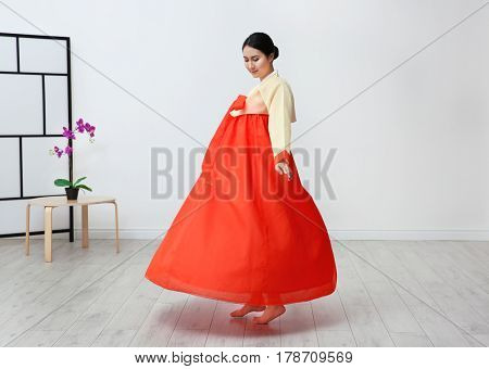 Beautiful young woman in Korean traditional costume dancing at home