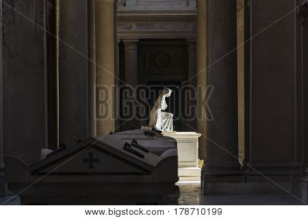 BOLOGNA,ITALY-DECEMBER 7,2016:Statue of woman praying inside monumental cemetery of the Certosa in Bologna during a sunny day.