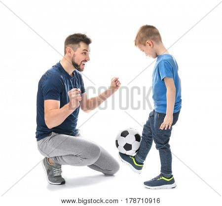 Handsome man and his son with soccer ball on white background