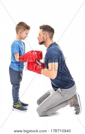 Father and son during boxing training, on white background