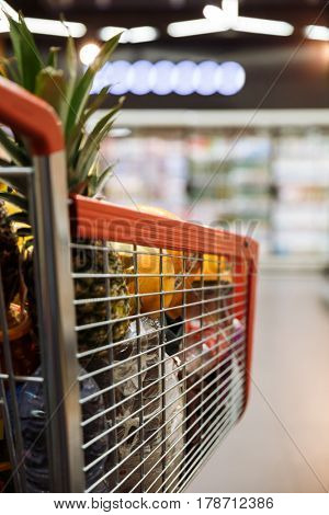 Image of a lot of fruits in shopping trolley in supermarket.