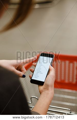 Cropped image of young lady standing in supermarket looking at list of purchases in phone.