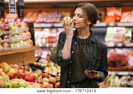 Picture of cheerful young lady standing in supermarket holding and smells apple. Eyes closed.