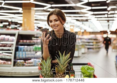 Picture of young cheerful woman in supermarket with shopping trolley choosing products and using phone. Looking aside.
