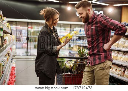 Image of young smiling loving couple in supermarket with shopping trolley choosing products. Looking at oil.