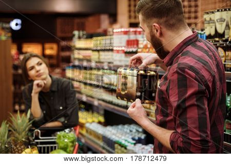 Image of young loving couple in supermarket with shopping trolley choosing products. Angry woman looking at man holding beer.