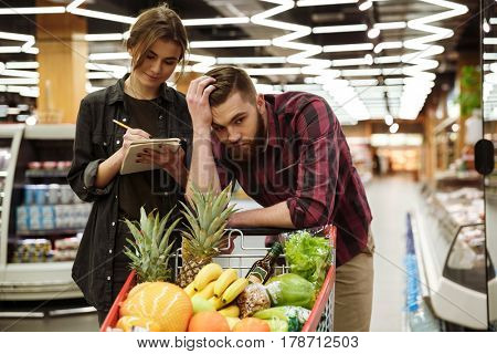 Picture of young loving couple in supermarket with shopping trolley choosing products. Tired man looking aside.