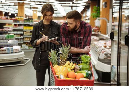 Image of young concentrated loving couple in supermarket with shopping trolley choosing products. Looking at notebook.