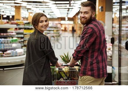 Image of young smiling loving couple in supermarket with shopping trolley choosing products. Looking at camera.