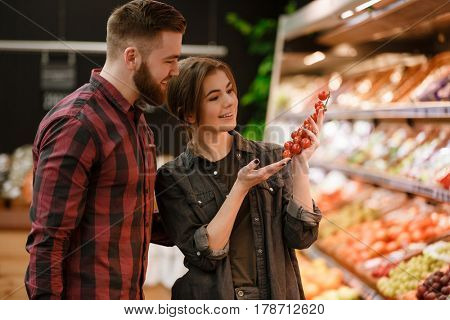 Photo of happy young loving couple standing in supermarket choosing vegetables. Looking aside.