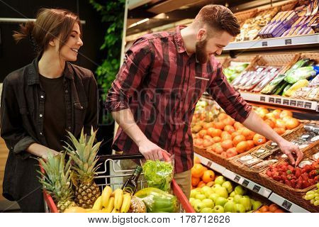 Image of young happy loving couple in supermarket with shopping trolley choosing fruits. Looking aside.