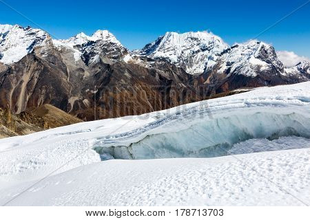 High Altitude Mountains View with snowy Peaks and large and dangerous Crevasse on foreground