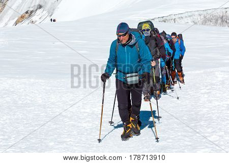 Mature Guide in high altitude Boots and other Gear leading diverse Group of Mountain Climbers on ascent to Himalaya Peak walking on snowy Glacier