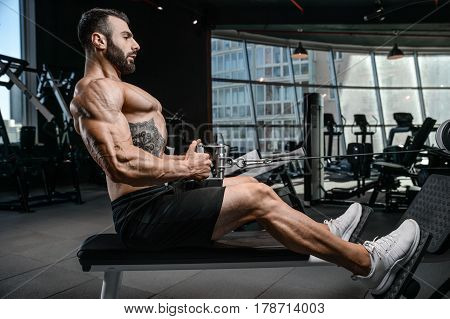 Handsome power athletic man on diet training pumping up back muscles pull up. Strong bodybuilder with six pack perfect abs back shoulders biceps triceps and chest