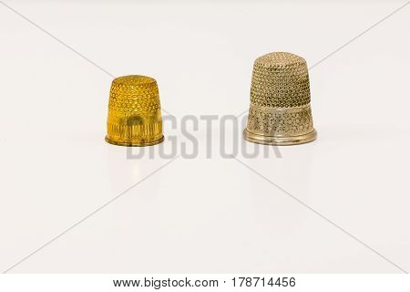 one thimble for sewing clothing and one thimble for sewing carpeting.