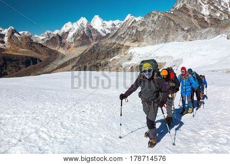 Severe Mountain Climbers in warm weather protective Clothing walking up on Glacier with climbing Gear and Backpacks against iconic Himalaya scenery on Background