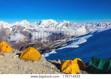Orange Tents of high Altitude Camp of Mountain Climbers Expedition in Himalaya Nepal in the evening majestic snowy summits on Horizon