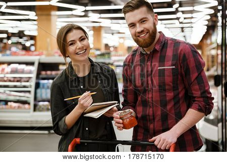 Photo of cheerful young loving couple standing in supermarket choosing products while reading notes at notebook. Looking at camera.