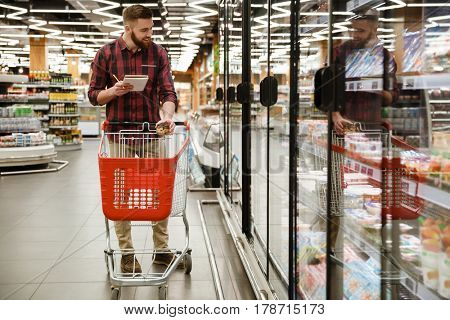 Photo of cheerful young man standing in supermarket choosing products while reading notes at notebook. Looking aside.