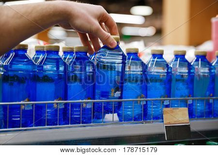 Cropped photo of young man standing in supermarket choosing water.