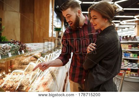 Image of happy young loving couple standing in supermarket choosing cake. Looking aside.