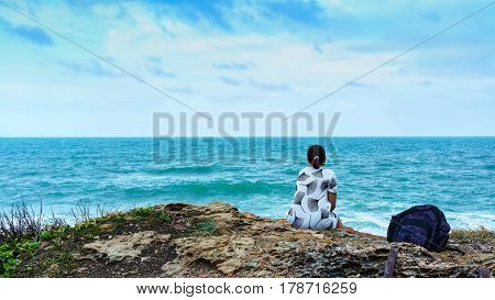 Asian woman sitting lonely on the rock looking at the sea at Khao Laem Ya National Park Rayong Thailand