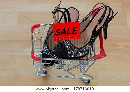 Pair of beautiful black velvet high heel shoes for ladies inside mini shopping push cart with red SALE card on it, on wooden background