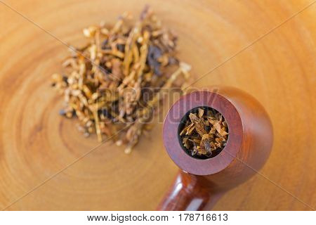 Closeup of classic blended aromatic pipe tobacco with vanilla flavor on bright wooden background