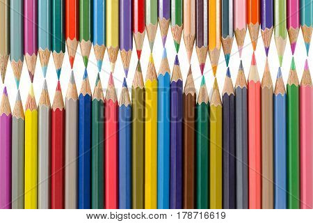 Variety of colored pencils arranged as a wave form. School art supplies isolated on white background