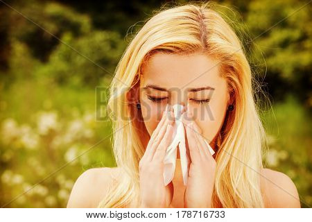 Unhappy woman with paper napkin sneezing.