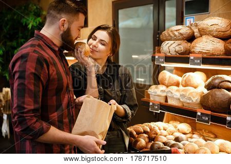 Image of young cheerful loving couple in supermarket smells and choosing pastries.