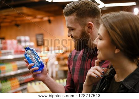 Picture of young cheerful loving couple in supermarket choosing water. Looking aside.
