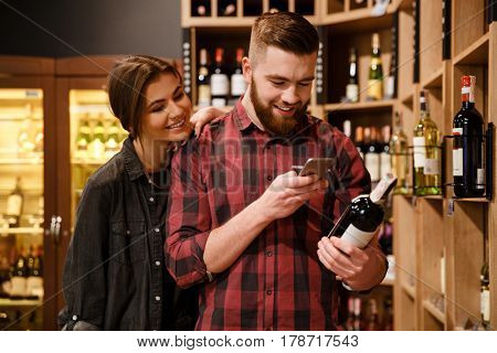 Photo of young concentrated cheerful loving couple in supermarket choosing alcohol. Looking aside.