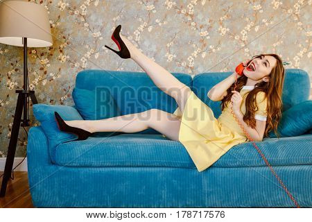 Side view of happy woman in yellow dress which lying on sofa and talking at handset