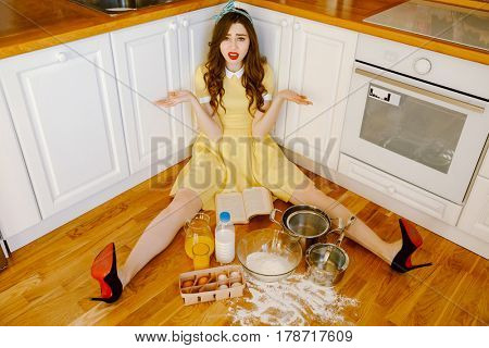 Picture of confused young pin-up woman with red lipstick sitting on floor at kitchen and cooking. Looking at camera.