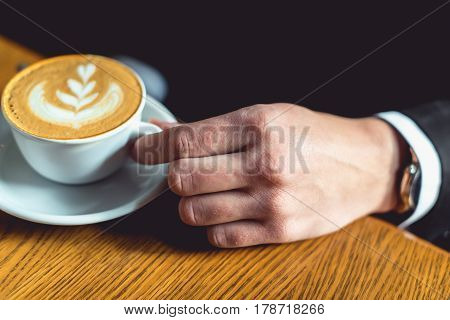 man's hand in a suit holding a cup of coffee. wodden table