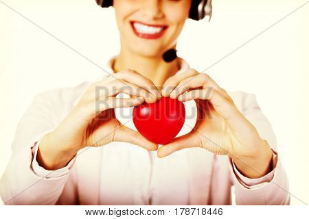 Happy call center woman holding heart toy