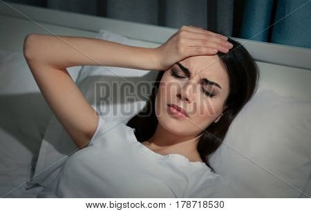 Beautiful young woman suffering from headache while lying in bed at night