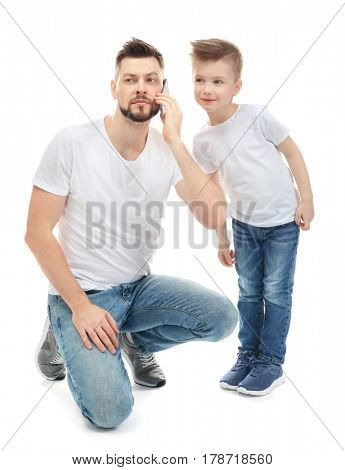 Little boy and his father talking by mobile phone, on white background